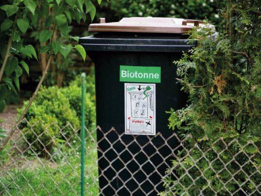 Biomülltonne hinter einem Maschendrahtzaun