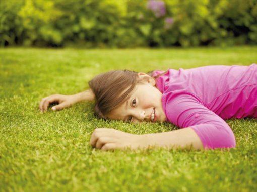 Mädchen liegt auf dem Rasen und guckt in die Kamera