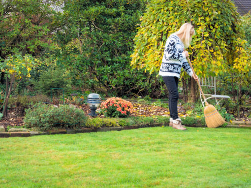 Frau im dicken Wollpulli fegt im Herbstgarten.