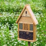 Insektenhotel aus Holz in einer Blumenwiese
